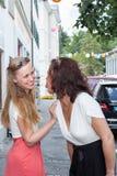 行动两名嬉戏的妇女幼稚在城市边路 图库摄影