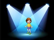 行动在阶段的中心的一个小女孩 图库摄影