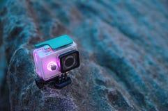 行动照相机在岩石站立 在防水防护箱子的照相机有光亮二极管显示的 旅游小配件 正面图 库存图片