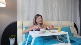 行动照相机给一名妇女在吃在立场的一顿可口早餐的床上 股票录像