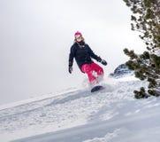 行动的女子挡雪板在山 免版税库存图片