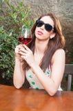 行动的女孩拿着杯酒和确信 库存照片
