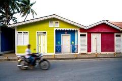 行动的未认出的人在摩托车在Las Terrenas,多米尼加共和国的中心通过五颜六色的木房子 库存照片