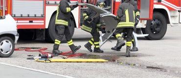 行动的消防员在与汽车的一次公路事故期间分开 免版税库存图片