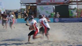 行动的美国橄榄球运动员在海滩的一场比赛期间在一个晴天 股票录像