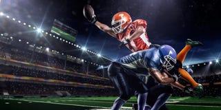 行动的美国橄榄球运动员对体育场 免版税库存照片
