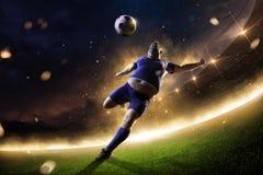 行动的肥胖足球运动员 火的体育场 免版税图库摄影