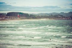 行动的Kitesurfing人在Brusand海滩,挪威的风雨如磐的日落晚上 库存图片