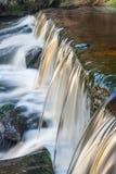 行动落在测流堰的被弄脏的小河 免版税图库摄影
