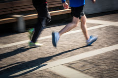 行动被弄脏的赛跑者的脚在城市环境里 库存图片