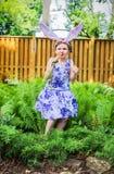 行动象兔宝宝的女孩吃红萝卜 免版税库存图片