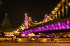 行动骑马在明亮的桥梁背景,城市夜照明,行动迷离的骑自行车者剪影的被弄脏的图象 免版税库存照片