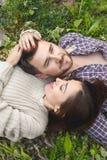 行家一对爱恋的夫妇在草放置 库存图片
