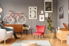 行家与沙发的客厅内部有绿色毯子的,红色a 免版税库存照片