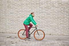 年轻行家人乘坐的固定的齿轮自行车 库存照片