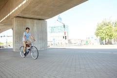 年轻行家人乘坐的固定的齿轮自行车 图库摄影