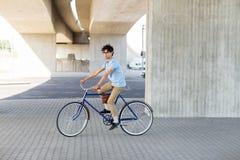 年轻行家人乘坐的固定的齿轮自行车 免版税库存图片