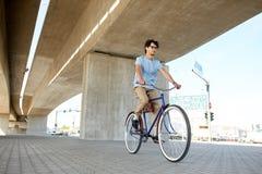 年轻行家人乘坐的固定的齿轮自行车 免版税图库摄影