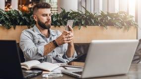 行家人在咖啡馆坐,使用智能手机,研究两台膝上型计算机 商人读在电话的一个信息消息 免版税库存照片