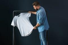 行家人在牛仔布衬衣、立场户内反对黑暗的墙壁背景和神色穿戴了在白色T恤杉 免版税图库摄影