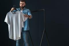 行家人在牛仔布衬衣穿戴了和牛仔裤、立场户内和神色在晒衣架的白色T恤杉在他的手上 库存照片
