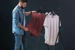 行家人在牛仔布衬衣穿戴了和牛仔裤、立场户内和神色在晒衣架的白色T恤杉在他的手上 图库摄影