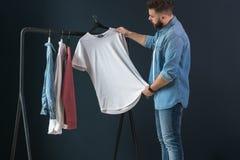 行家人在牛仔布衬衣穿戴了和牛仔裤、立场户内和神色在晒衣架的白色T恤杉在他的手上 免版税库存图片