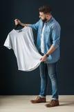 行家人在牛仔布衬衣穿戴了和牛仔裤、立场户内和神色在晒衣架的白色T恤杉在他的手上 免版税库存照片