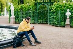 行家人室外射击有胡子的在冲浪社会网络的喷泉附近穿戴了时髦休息在公园使用他的手机 免版税图库摄影