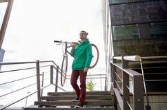 年轻行家人运载的固定的齿轮自行车在城市 库存照片