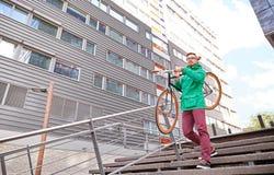 年轻行家人运载的固定的齿轮自行车在城市 图库摄影