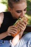行家佩带的摆在吃大三明治 库存图片