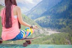 行家做瑜伽的时尚女孩,放松在滑板在山 库存图片