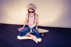 行家听到音乐的女孩溜冰板者 免版税库存图片