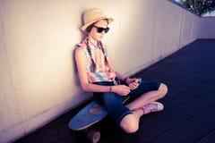行家听到音乐的女孩溜冰板者 免版税库存照片