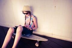行家听到音乐的女孩溜冰板者 免版税图库摄影