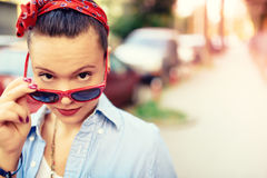 行家女孩佩带的太阳镜和时装配件 做在生活方式画象的微笑的女孩滑稽的面孔 库存照片