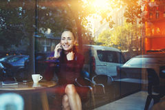 年轻行家女孩叫与手机,当坐在当代咖啡店时 免版税库存图片