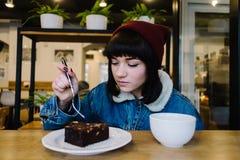 年轻行家女孩吃鲜美巧克力蛋糕和饮用的热的咖啡在一个美味的咖啡馆 免版税库存图片