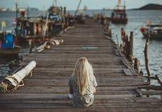 行家女孩坐在落日的光芒的木码头 一个假期在泰国 回到照相机 假期 图库摄影