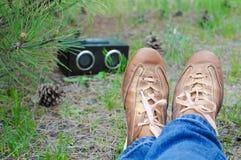 行家女孩布朗鞋子牛仔裤放松在草和听的音乐的在绿色夏天公园 库存图片
