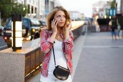 年轻行家女孩机智美好的微笑谈话在巧妙的电话,当享受好温暖的晚上,华美的愉快的女性讲的cel时 库存照片