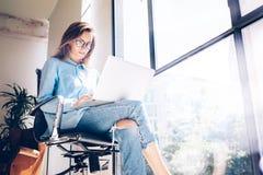 行家女孩用途膝上型计算机巨大的顶楼演播室 研究处理工作的学生 工作创造性的起动的年轻女商人 库存照片