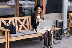 行家女孩的画象在摆在时髦的衣裳穿戴了,当与网书坐在边路咖啡馆时的一条舒适长凳 免版税库存照片