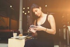 行家女孩键入在手机的正文消息,当坐边路咖啡馆时大阳台  免版税库存照片
