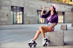 行家女孩饮料水和休息在活跃时间以后 免版税库存图片