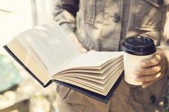 行家女孩读一本书并且喝咖啡 库存图片