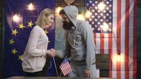 行家妇女和人震动移交美国人和欧盟旗子 在美国人和欧盟旗子的握手 ?? 股票视频