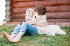 年轻行家妇女女孩白色羊羔皮狗剥去了牛仔裤 免版税图库摄影