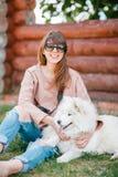 年轻行家妇女女孩白色羊羔皮狗剥去了牛仔裤 免版税库存图片